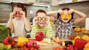 niños felices con alimentos ricos en vitaminas