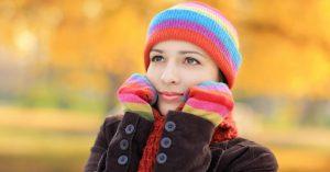 Chica usando guantes y gorro de arcoiris