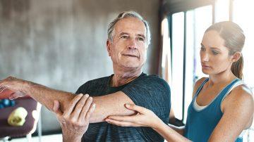 Persona cuidando a señor con osteoporosis