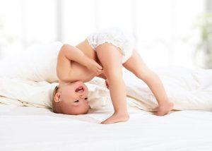 Bebé con cabeza en la cama