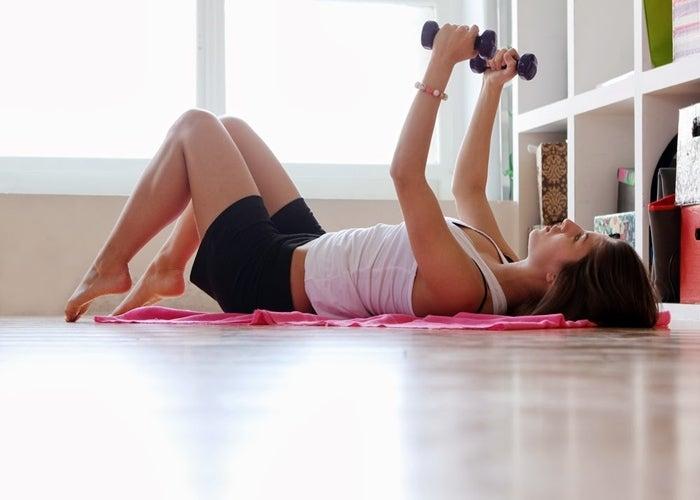 Chica haciendo ejercicio con pesas en el piso