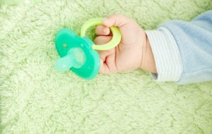Chupón verde en mano de bebé