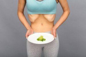 Chica anoréxica con plato de comida