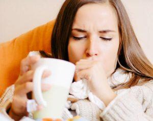 Chica tomando té para la tos con flemas