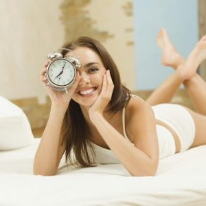 Chica sonriente con reloj en mano
