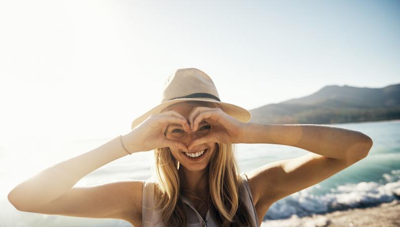 Chica feliz haciendo un corazón con las manos