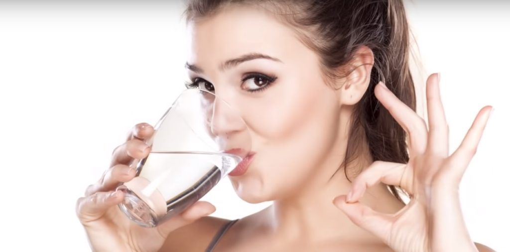 Mujer tomando agua para la náuseas